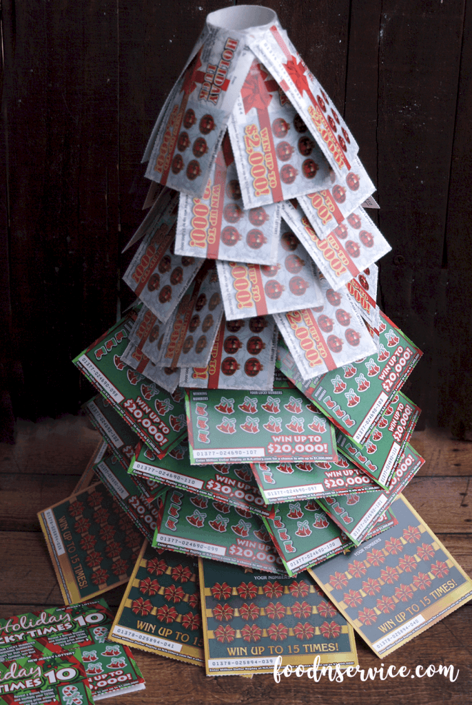 Build up the layers with the remaining $1 scratch off tickets. As you can see, I built 4 more layers with the top layer of the tree having 5. When you get to the top of the tree, you're going to want tape them down together. Once you tape them down to the top portion of the toilet paper rolls, you'll wind up getting the form of your tree! The pressure of the top layer tickets will force the others down more!
