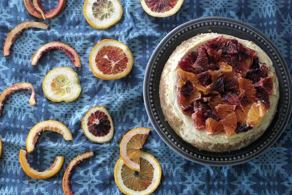instant pot blood orange cheesecake on blue napkin with sliced blood oranges