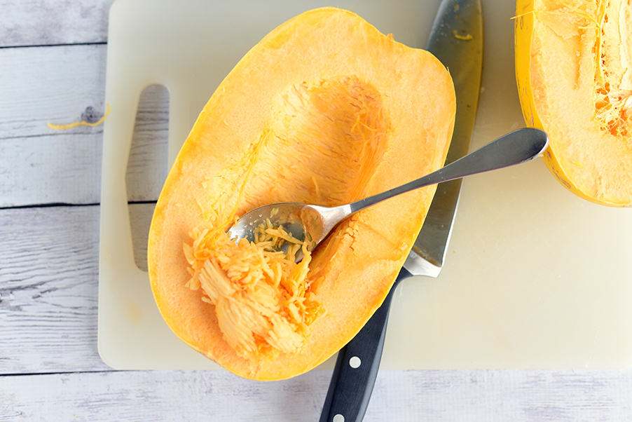 spaghetti squash being scooped out with a spoon on a white cutting board