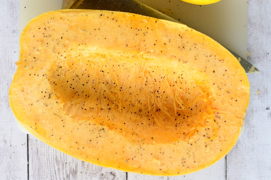 spaghetti squash cut open and seasoned with salt & pepper