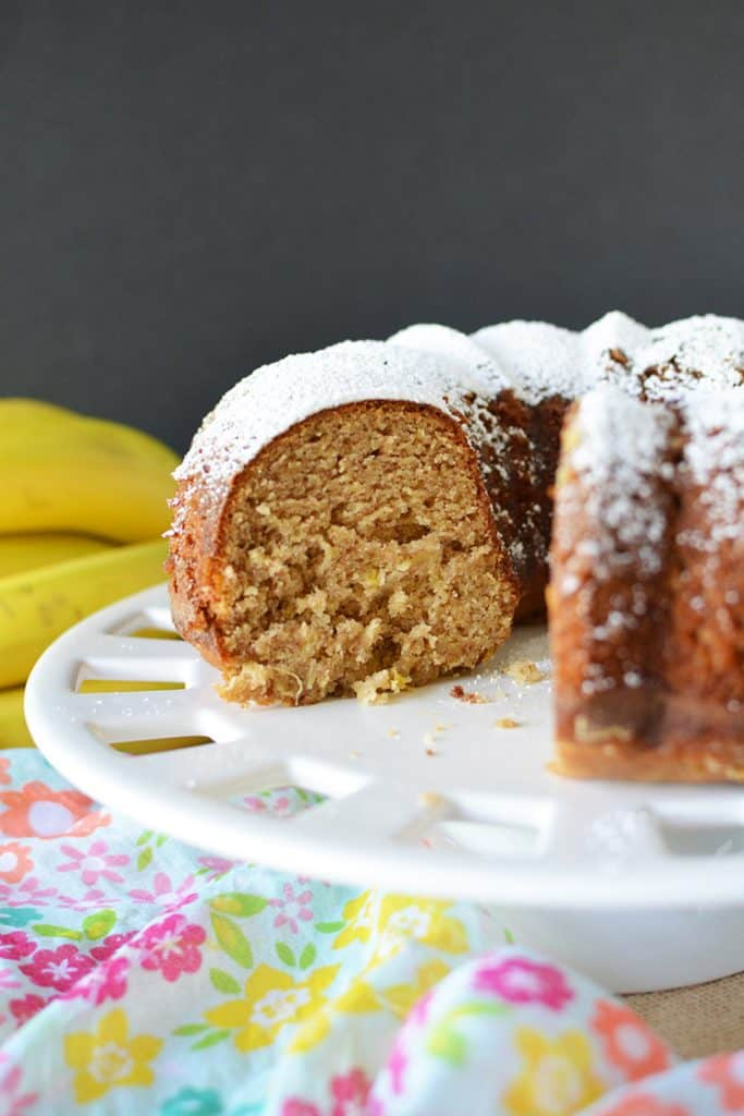 pineapple banana cake on a white platter with bananas in the background