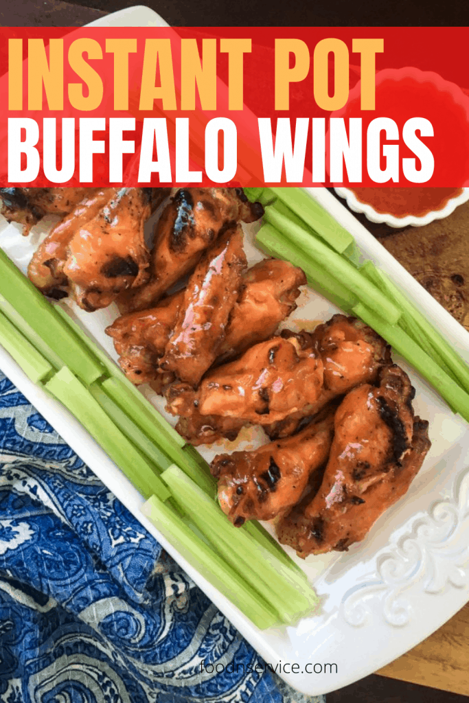 instant pot buffalo wings on a white plate and blue paisley napkin