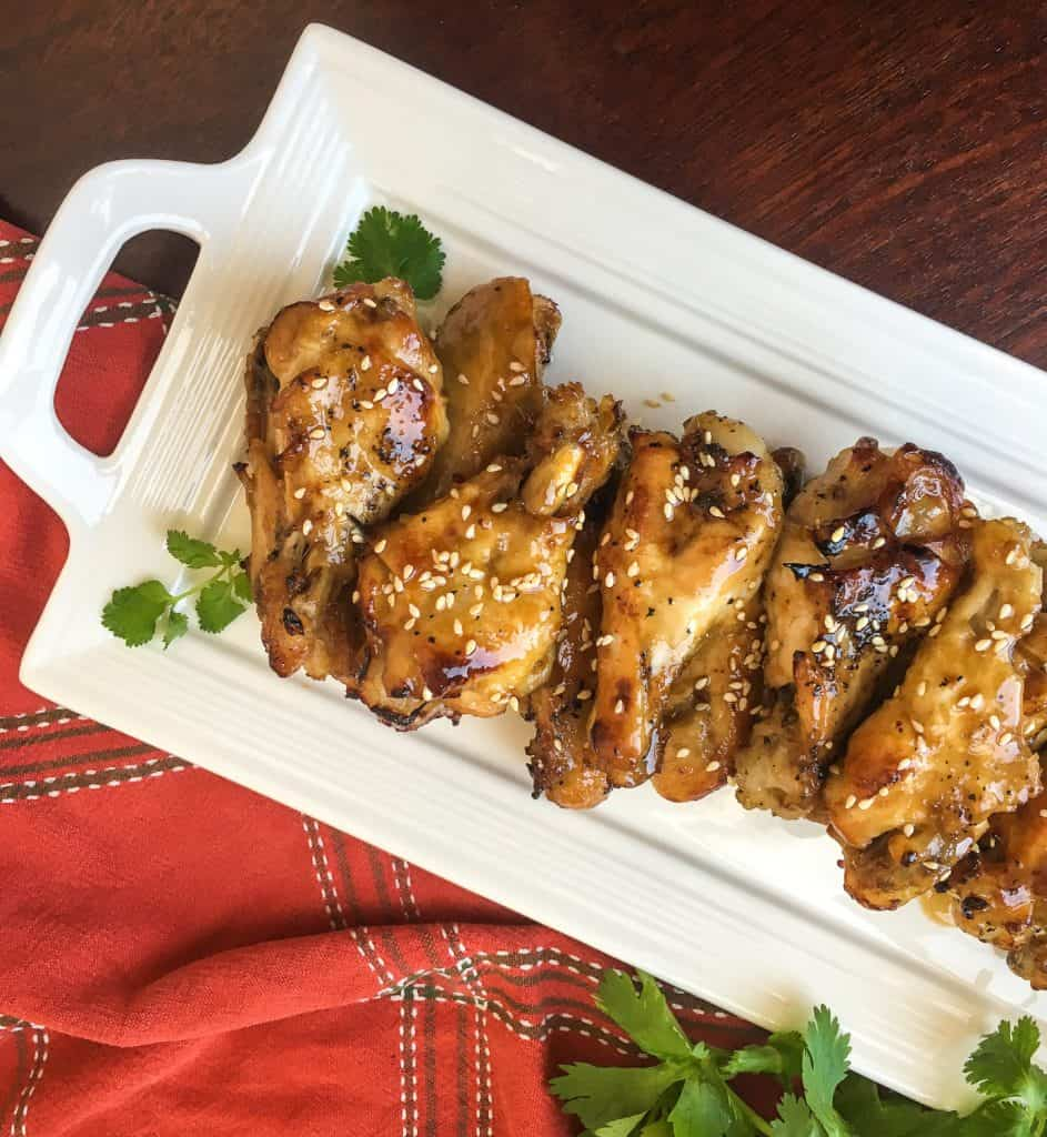 instant pot sesame garlic wings on a white plate with red background