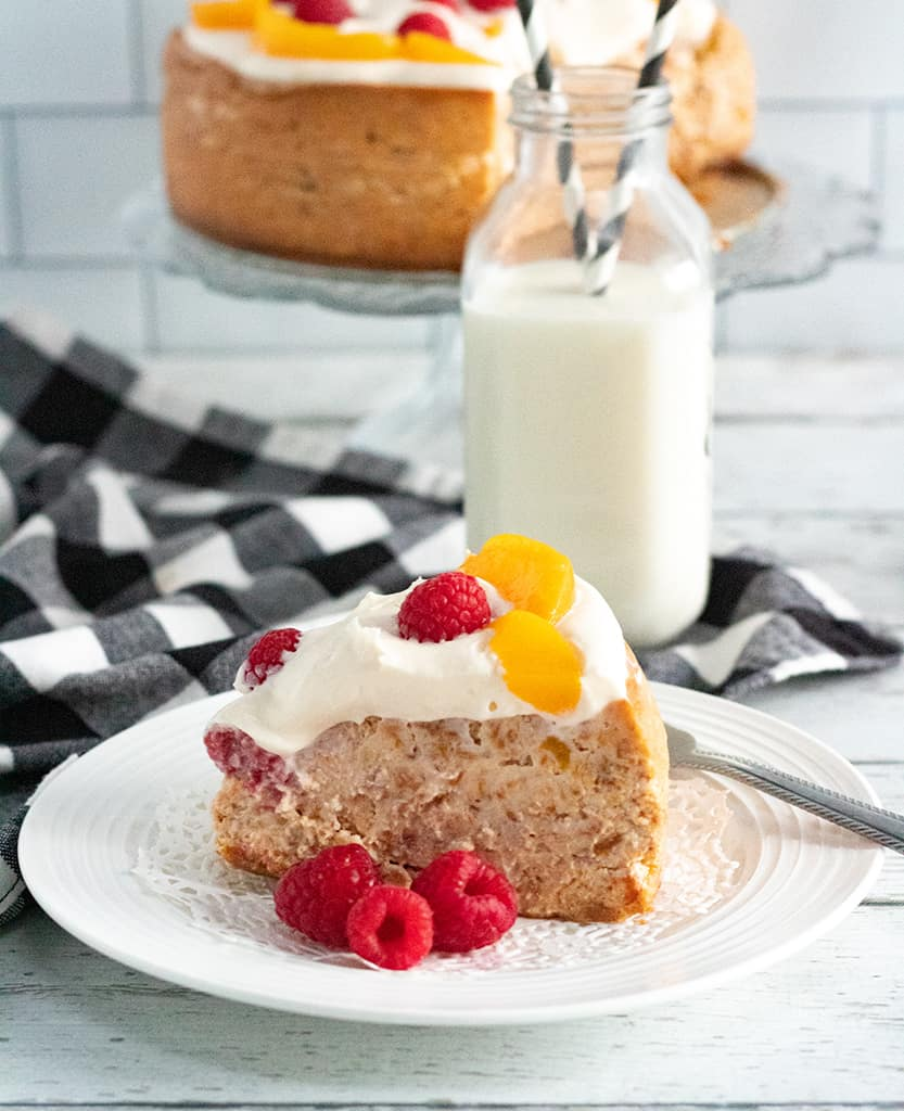 a slice of instant pot rapsberry peach cheesecake on a plate with a glass of milk