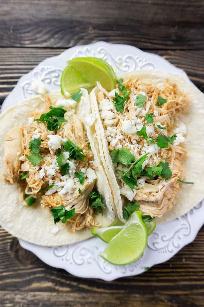Instant pot key lime chicken tacos with fresh cilantro and queso blanco cheese