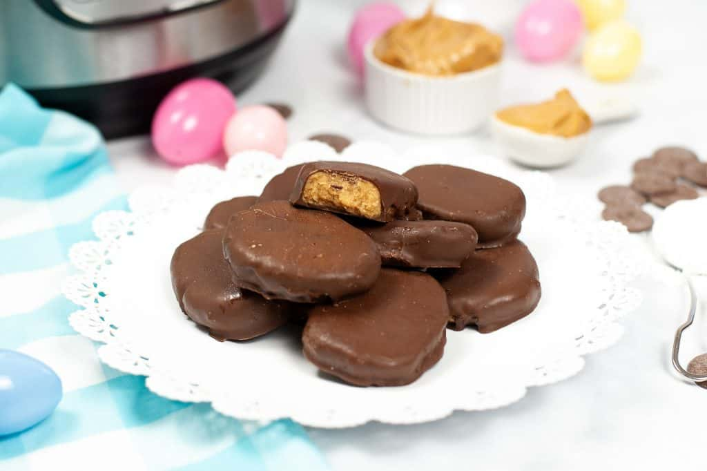 instant pot reeses peanut butter eggs on a white plate in front of a pressure cooker